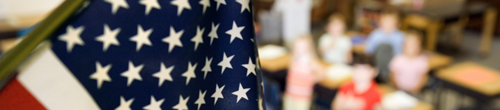 American flag hanging in a classroom with students in the background